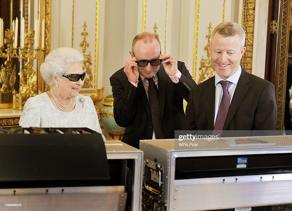 Queen Elizabeth II with producer John McAndrew and director John Bennett (R) watch the recording of her Christmas message to the Commonwealth which is to be broadcast in 3D for the first in the White Drawing Room of Buckingham Palace on December 7, 2012 in London, England.