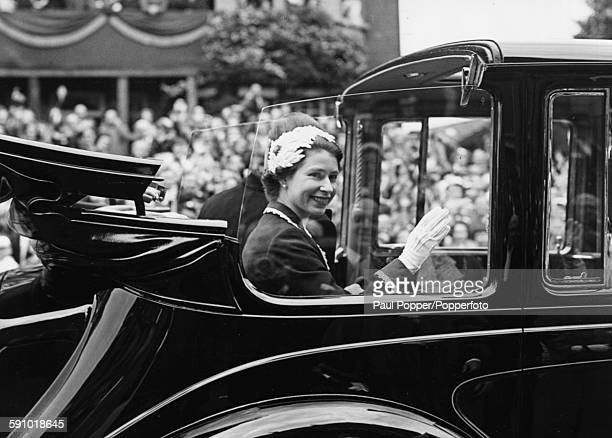 Queen Elizabeth II with the Duke of Edinburgh sitting next to her waves from the back of a car to residents of Hampstead during her Coronation drive...