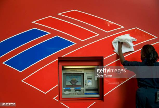 Queen Elizabeth Johnson an employee of Redlee/SCS Group cleans the front of an atm machine across the street from Bank of America's headquarters on...