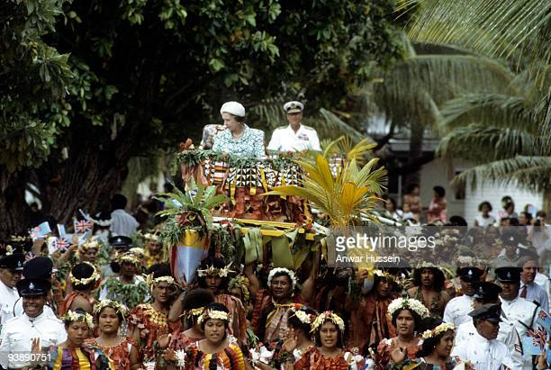 Queen Elizabeth ll and Prince Philip Duke of Edinburgh are carried ashore on local canoes as they arrive on October 27 1982 in Tuvalu