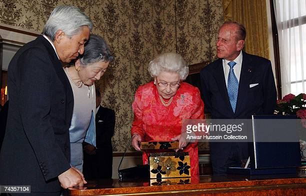 Queen Elizabeth ll and Prince Philip Duke of Edinburgh present Emperor Akihito and Empress Michiko of Japan with a silver rimmed crystal bowl and in...