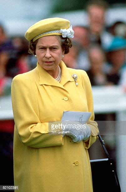 Queen Elizabeth Ll Frowning As She Watches The Racing At The Derby On 1st June 1988 The Queen Is Wearing A Yellow Hat Trimmed With White Flowers...
