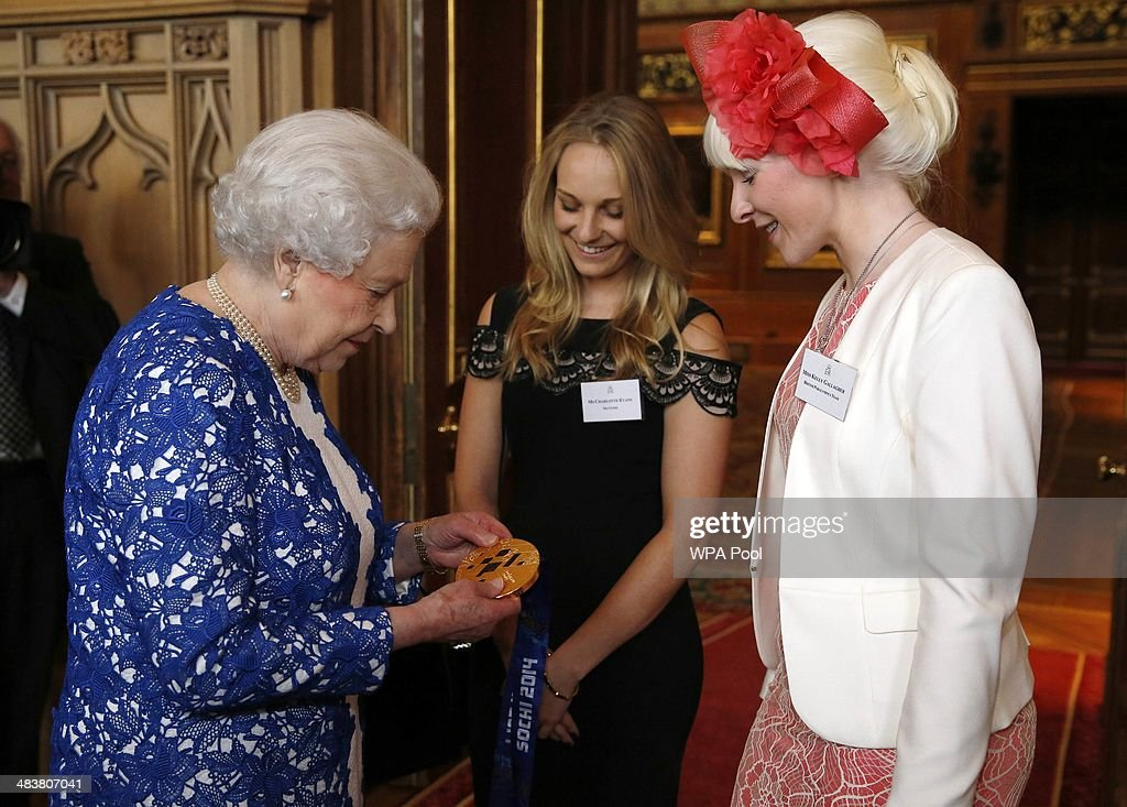 Queen Elizabeth ll holds the gold medal of Paralympic skier Kelly Gallagher (R) from Northern Ireland as her guide Charlotte Evans looks at a Northern Ireland-themed reception at Windsor Castle on April 10, 2014 in Windsor, United Kingdom. The event was organised as part of Irish President Michael D Higgins' four-day state visit. The visit comes three years after Queen Elizabeth II made a groundbreaking trip to the republic, which helped to heal deep-rooted unease and put British-Irish relations on a new footing.