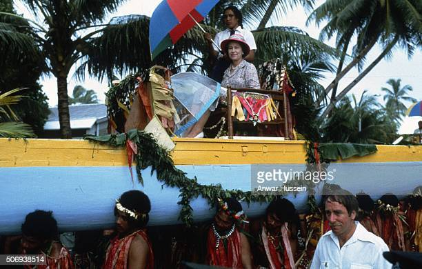 Queen Elizabeth ll is carried in a war canoe down the main street in Tuvalu during her tour of the South Pacific on October 27 1982 in Tuvalu South...