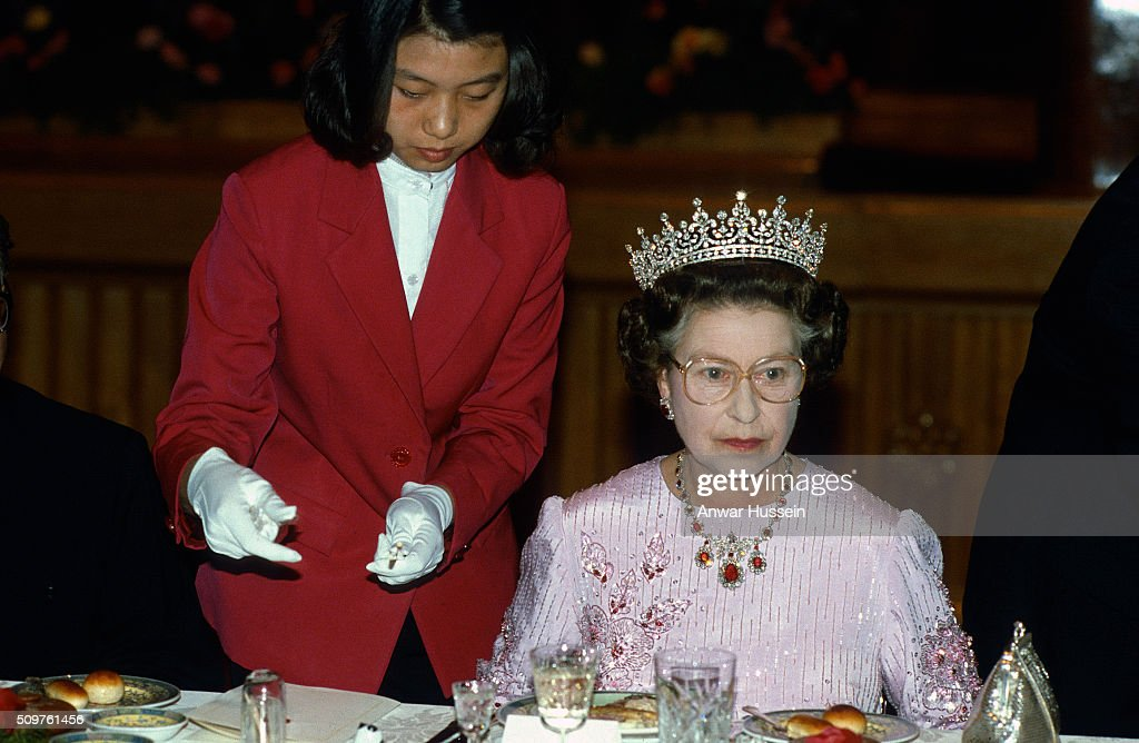 Queen Elizabeth ll is offered chopsticks during a State Banquet on October 13 ,1986 in Peking, China. The Queen is wearing the tiara known as 'Granny's Tiara' and a pink dress decorated with tree peony blossom, the national flower of China, designed by Ian Thomas.