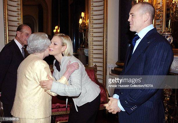Queen Elizabeth ll kisses her granddaughter Zara Phillips as boyfriend English rugby player Mike Tindall looks on at a Buckingham Palace reception...