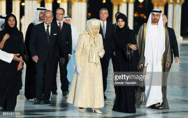 Queen Elizabeth ll wears a long gown and special headgear as she arrives at the Sheikh Zayed Mosque with Prince Philip Duke of Edinburgh and Prince...