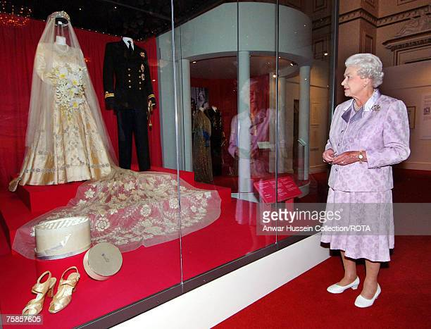 Queen Elizabeth looks at her 1947 wedding gown and 13 foot bridal trail designed by Norman Hartnell with the naval uniform worn by Prince Philip Duke...