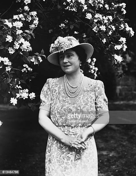 Queen Elizabeth of England wife of King George VI in front of some lilacs at Windsor Castle