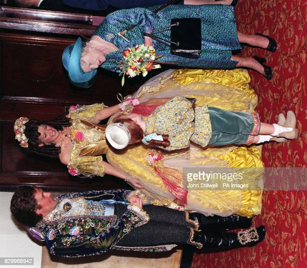 Queen Elizabeth the Queen Mother accepts a posey from sixyearold Samuel Clitherow who plays Chip in Disney's 'Beauty and the Beast' other cast...