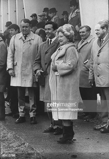 Queen Mother Elizabeth standing next to jockey turned author Dick Francis while watching The Windsor Races