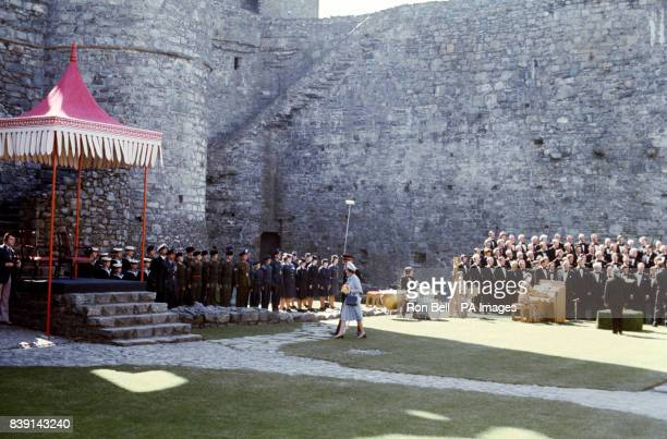 Queen Elizabeth walking to a dais at Harlech Castle with a male voice choir in attendance