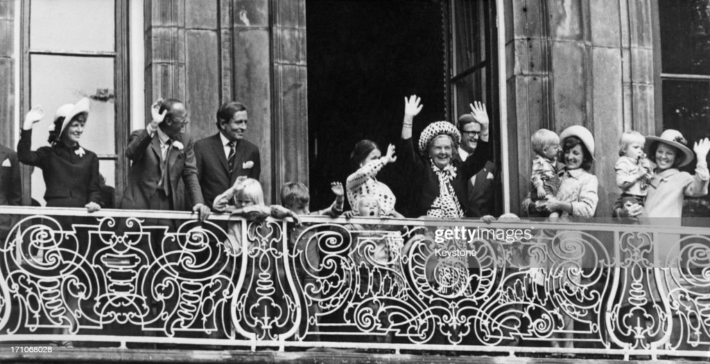 Queen Juliana of the Netherlands and members of the Dutch royal family wave from the balcony of the Lange Voorhout Palace in The Hague during...