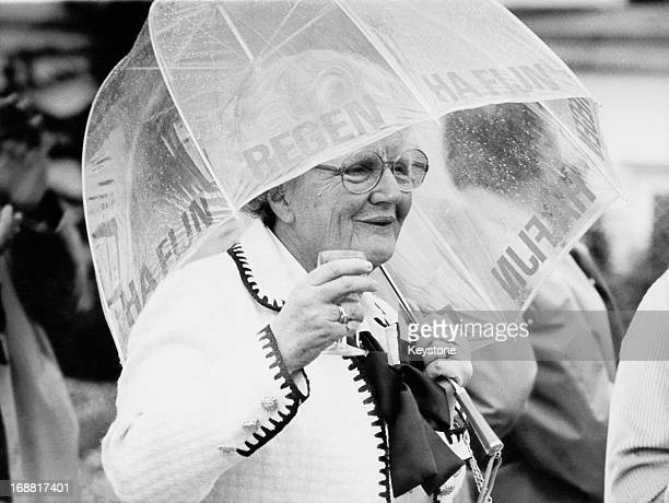 Queen Juliana of the Netherlands uses an umbrella to shield herself from the rain during a garden reception at Soestdijk Palace 28th May 1979