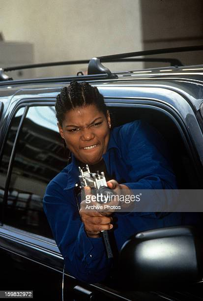 Queen Latifah firing an automatic gun out of the passenger's window of a car in a scene from the film 'Set It Off' 1996