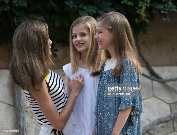 Queen Letizia of Spain speaks with her daughters Spanish crown princess Leonor and princess Sofia in the gardens at the Marivent Palace on the island...