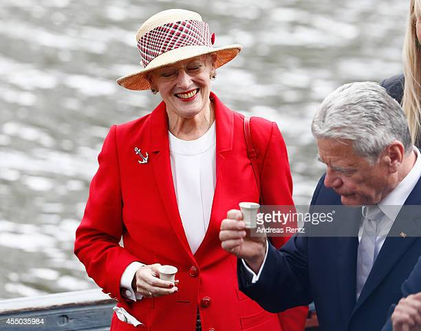 Queen Margrethe II of Denmark and German President Joachim Gauck have a shot upon their arrival to board the remake of a Viking ship on September 9...