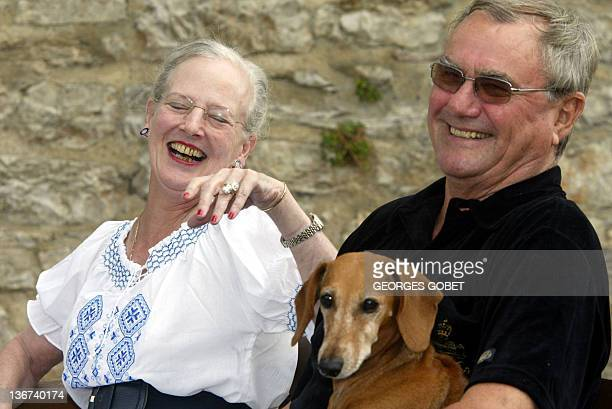 Queen Margrethe II of Denmark and her husband Prince Henrik share a joke in their garden before meeting journalists 11 August 2005 in the castle of...