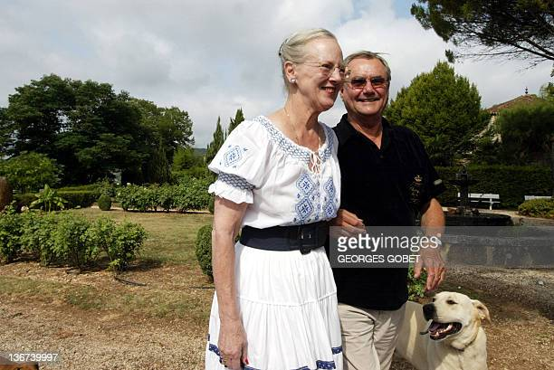 Queen Margrethe II of Denmark and her husband Prince Henrik stroll in their garden with the dog Pollock before meeting journalists 11 August 2005 in...