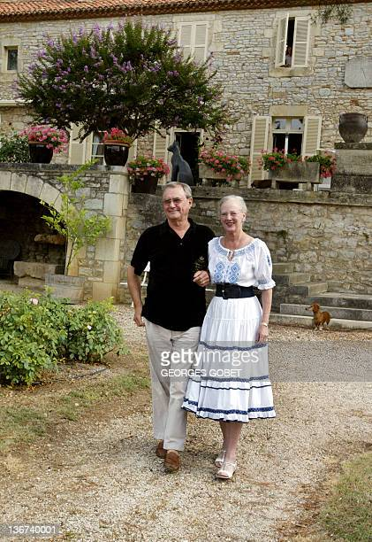 Queen Margrethe II of Denmark and her husband Prince Henrik stroll in their garden before meeting journalists 11 August 2005 in the castle of Caix...