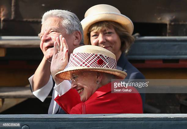 Queen Margrethe II of Denmark German President Joachim Gauck and German First Lady Daniela Schadt wave to onlookers aboard the remake of a Viking...