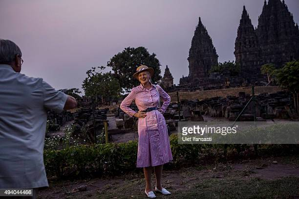 Queen Margrethe II of Denmark poses as her husband Prince Henrik takes her photograph during their visit at Prambanan temple on October 24 2015 in...