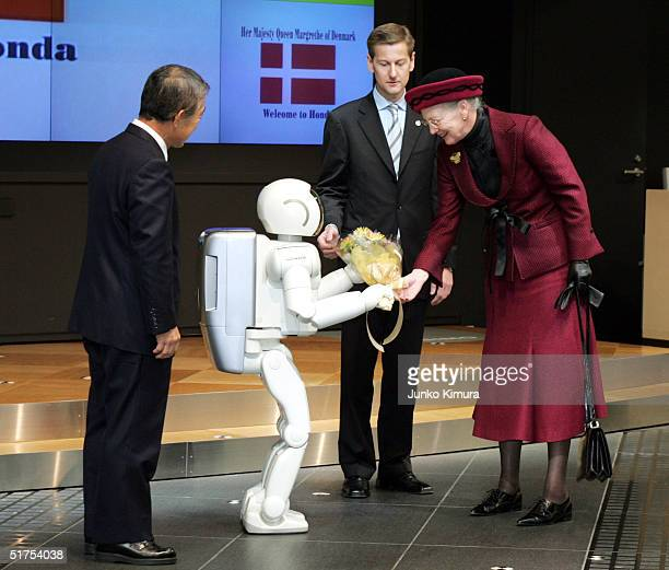 Queen Margrethe II of Denmark shakes hands with Honda's robot Asimo as Takeo Fukui president of Honda looks on at the showroom in the company's...