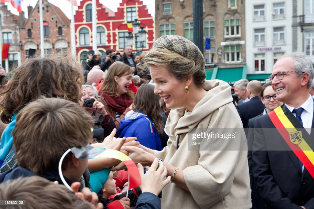 Queen Mathilde of Belgium (C) and Bruges' mayor Renaat Landuyt (R) meet citizens during the 'Joyous Entry' of the Belgian royal couple to present themselves to the public in Bruges, on October 25, 2013.