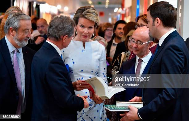 Queen Mathilde of Belgium leafs through books given to her by Director of Casterman publishing Simon Casterman and chief editor of the comics...