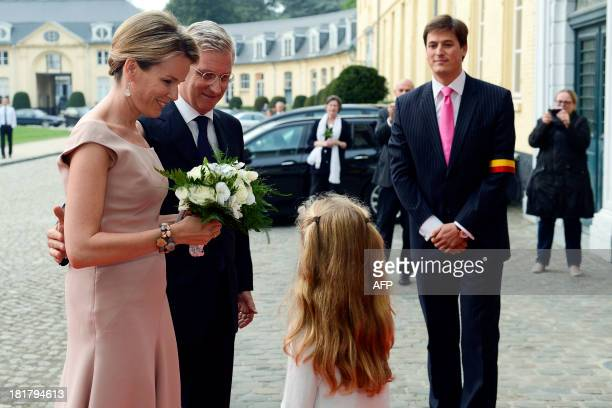 Queen Mathilde of Belgium stands beside King Philippe Filip of Belgium after receiving flowers before a concert in the church to honor the new King...