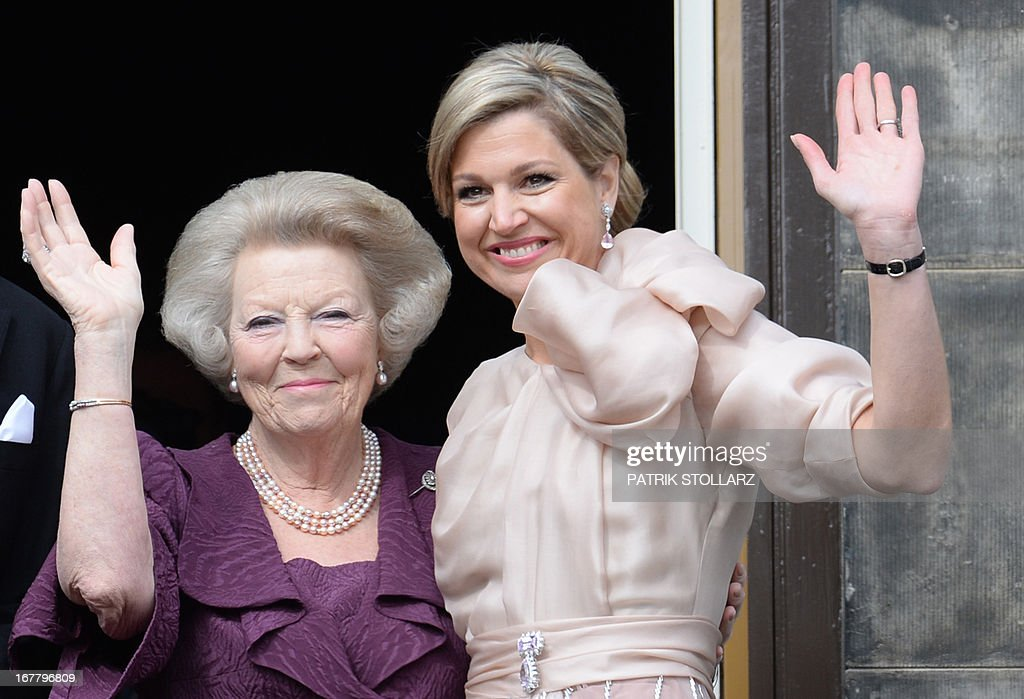 Queen Maxima (R) and Princess Beatrix (L) wave on April 30, 2013 to the crowd gathered on Dam Square from the balcony of the Royal Palace in Amsterdam, following the official abdication ceremony. AFP PHOTO / PATRIK STOLLARZ