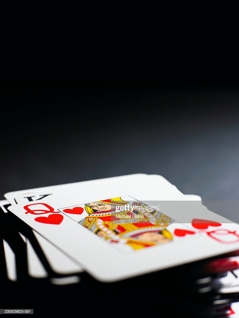 Queen of hearts on pile of playing cards, close-up : Stock Photo