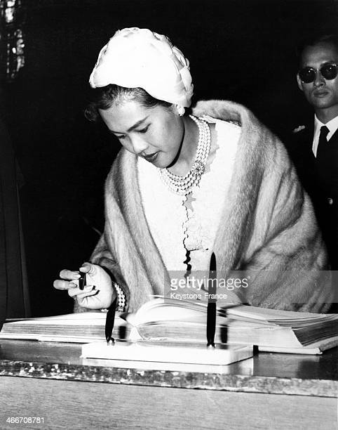 Queen Queen Sirikit Kitiyakara Of Thailand signs the visitors' book after the wreath lying ceremony on the tomb of the Unknown Warrior at Westminster...