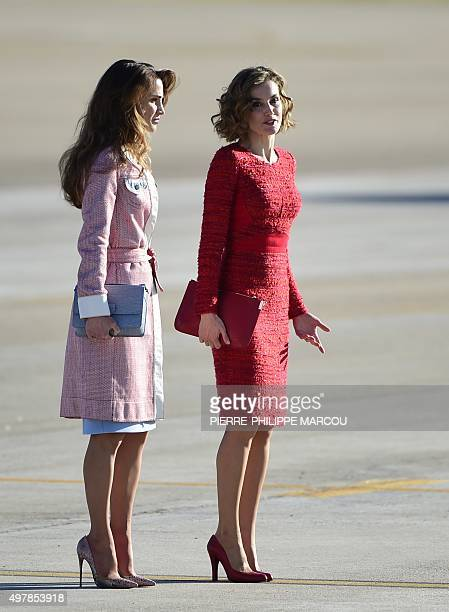 Queen Rania of Jordan and Queen Letizia of Spain stand after arriving at Madrid's Barajas Adolfo Suarez airport on November 19 2015 AFP PHOTO/...