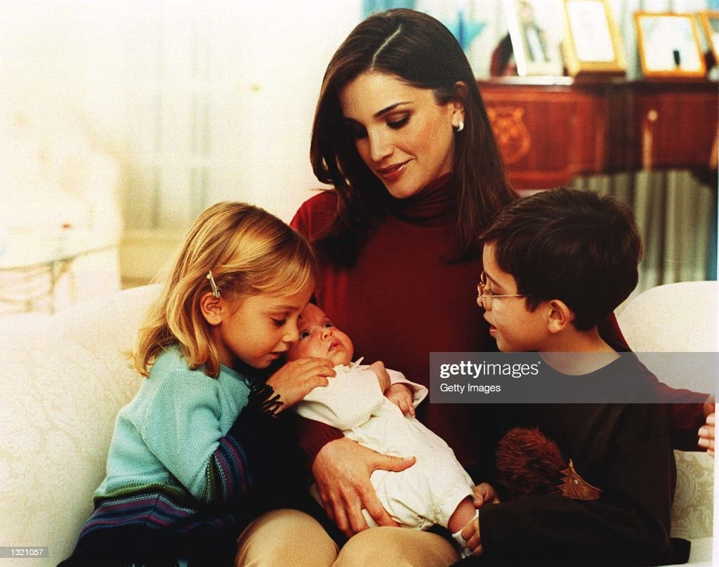 Queen Rania of Jordan holds Princess Salma in her arms November 20, 2000 in Amman, Jordan as Princess Eman, left, and Prince Hussein, right, look on.