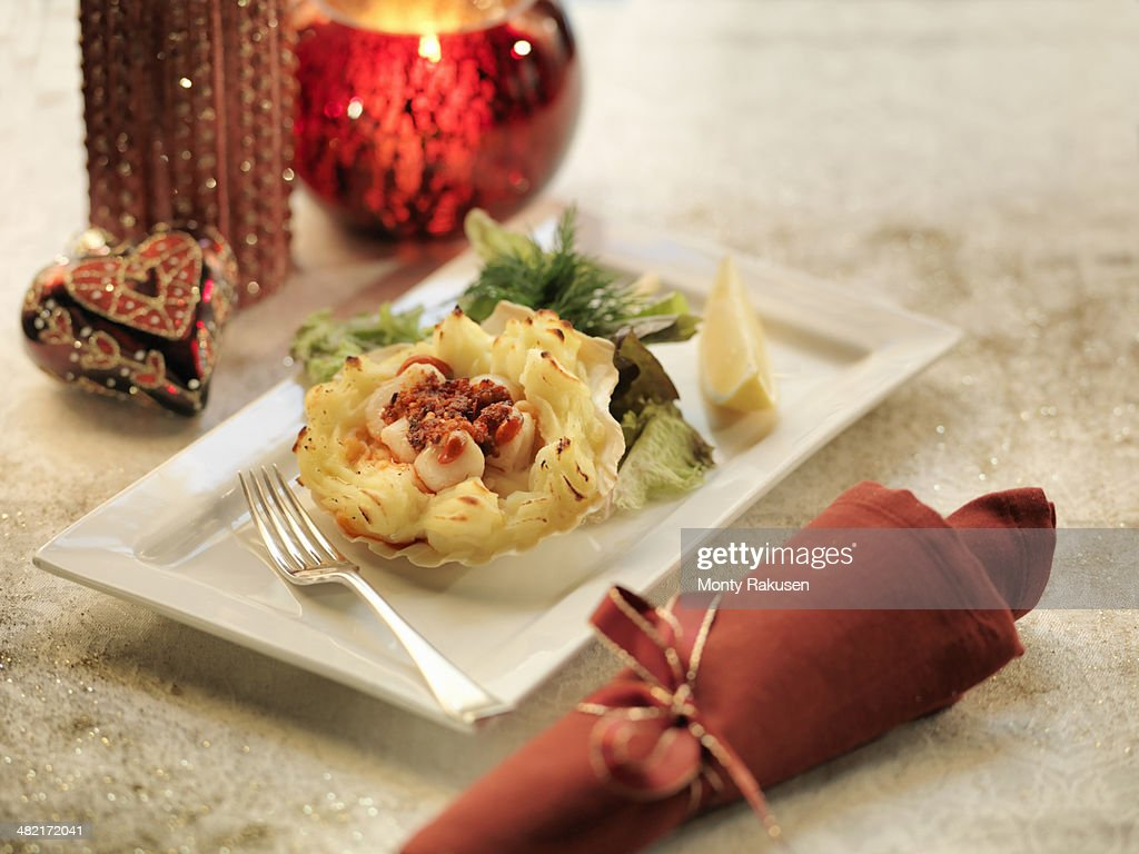 Queen scallops gratin with calabrian sausage on a mashed potato filled scallop shell amongst festive decorations