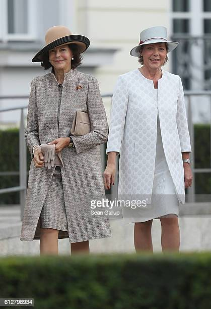 Queen Silvia of Sweden and German First Lady Daniela Schadt walk together upon the Swedish Royal Couple's arrival at Schloss Bellevue palace on...