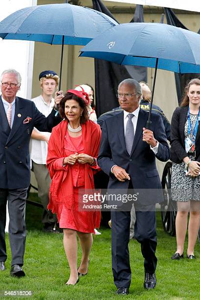 Queen Silvia of Sweden and King Carl XVI Gustaf of Sweden are seen in the rain during the opening ceremony of the CHIO 2016 on July 12 2016 in Aachen...