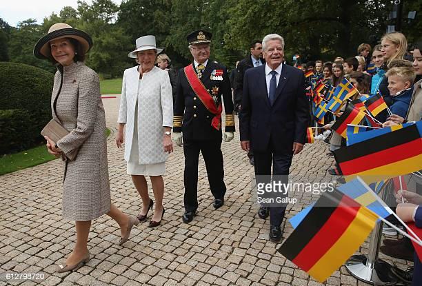 Queen Silvia of Sweden German First Lady Daniela Schadt King Carl XVI Gustaf of Sweden and German President Joachim Gauck walk past children upon the...
