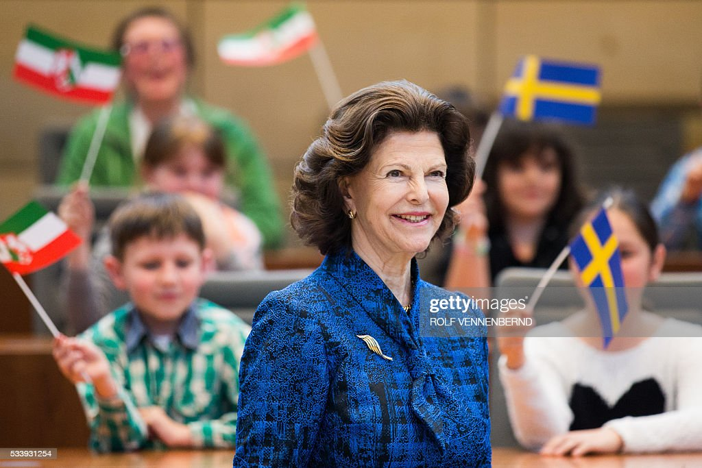 Queen Silvia of Sweden is welcomed by children as she visits the plenary hall of the regional parliament in Duesseldorf, western Germany, on May 24, 2016. / AFP / dpa / Rolf Vennenbernd / Germany OUT