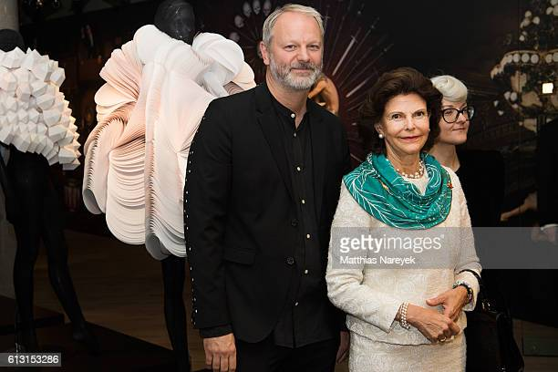 Queen Silvia of Sweden is welcomed by the artist Bea Szenfeld and Pompe Hedengren during the opening of a fashion exhibition at Bikini House on...