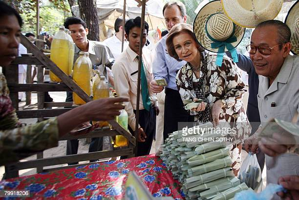 Queen Sofia of Spain buys palm sugar along a street during her visit to Siem Reap province some 314 kilometers northwest of Phnom Penh on February 22...