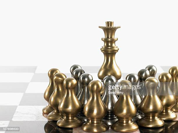 Queen surrounded by pawn chess pieces