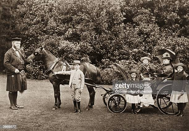 Queen Victoria with her grandchildren in a pony and trap in the garden at Osborne House on the Isle of Wight Her personal attendant John Brown stands...