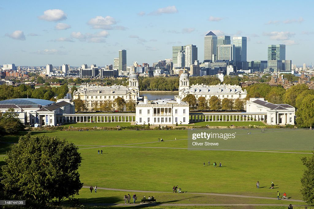 Queens House (front), Old Royal Naval College Domed (buildings), and National Maritime Museum (left) from Greenwich Park, with financial district in background.
