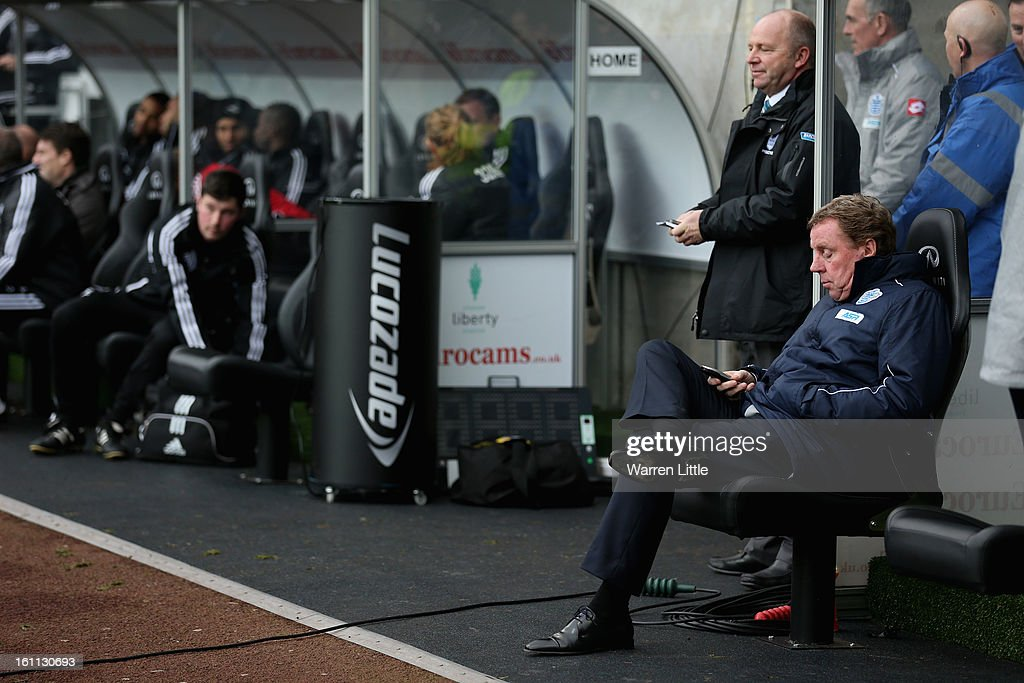 Queens Park Ranger manager Harry Rednapp chechs his phone during the Premier League match between Swansea City and Queens Park Rangers at Liberty Stadium on February 9, 2013 in Swansea, Wales.
