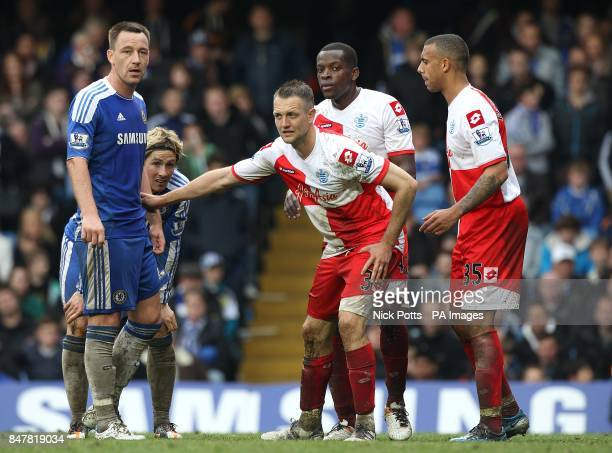 Queens Park Rangers' Anton Ferdinand and Clint Hill mark Chelsea's John Terry