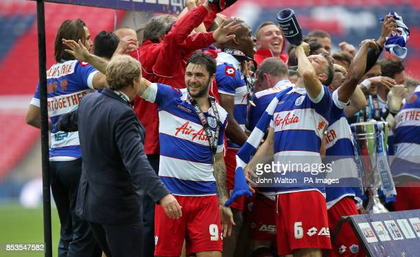 Queens Park Rangers' Charlie Austin Clint Hill and manager Harry Redknapp celebrate with champagne after the game