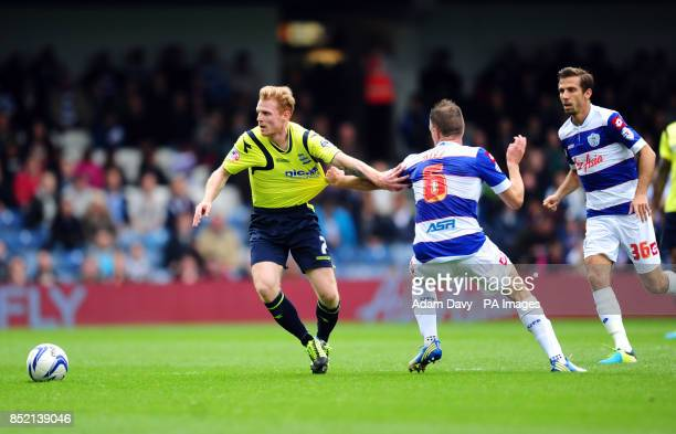 Queens Park Rangers' Clint Hill and Birmingham City's Chris Burke battle for the ball during the Sky Bet Championship match at Loftus Road London