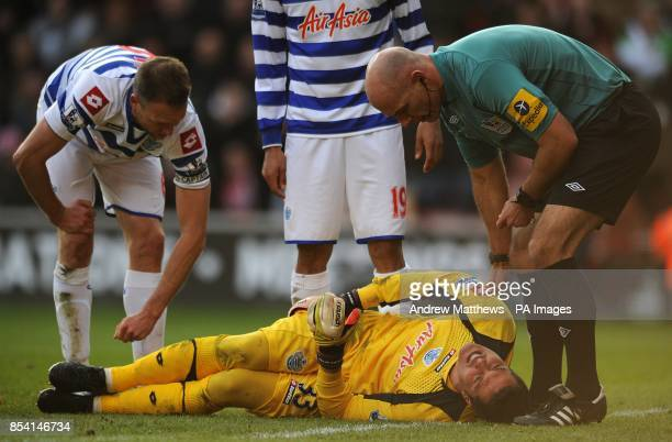 Queens Park Rangers' Clint Hill and referee Howard Webb check on goalkeeper Soares Julio Cesar as he lies injured
